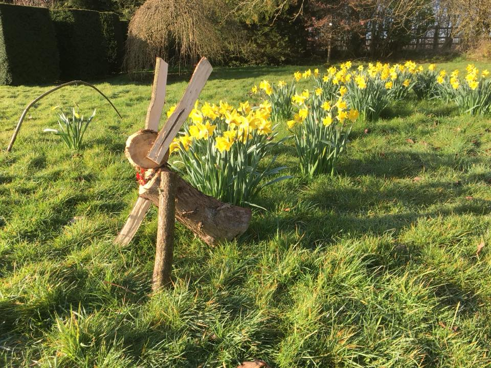 Wooden Easter bunny sitting in grass surrounded by daffodils